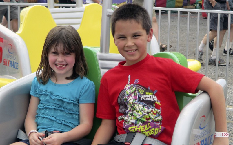 Cousins Ella Jenkins, left, of Maurertown , and Aiden Wood, Middletown, enjoy a ride at the Shenandoah County Fair.  Courtesy photo by Joye Wood
